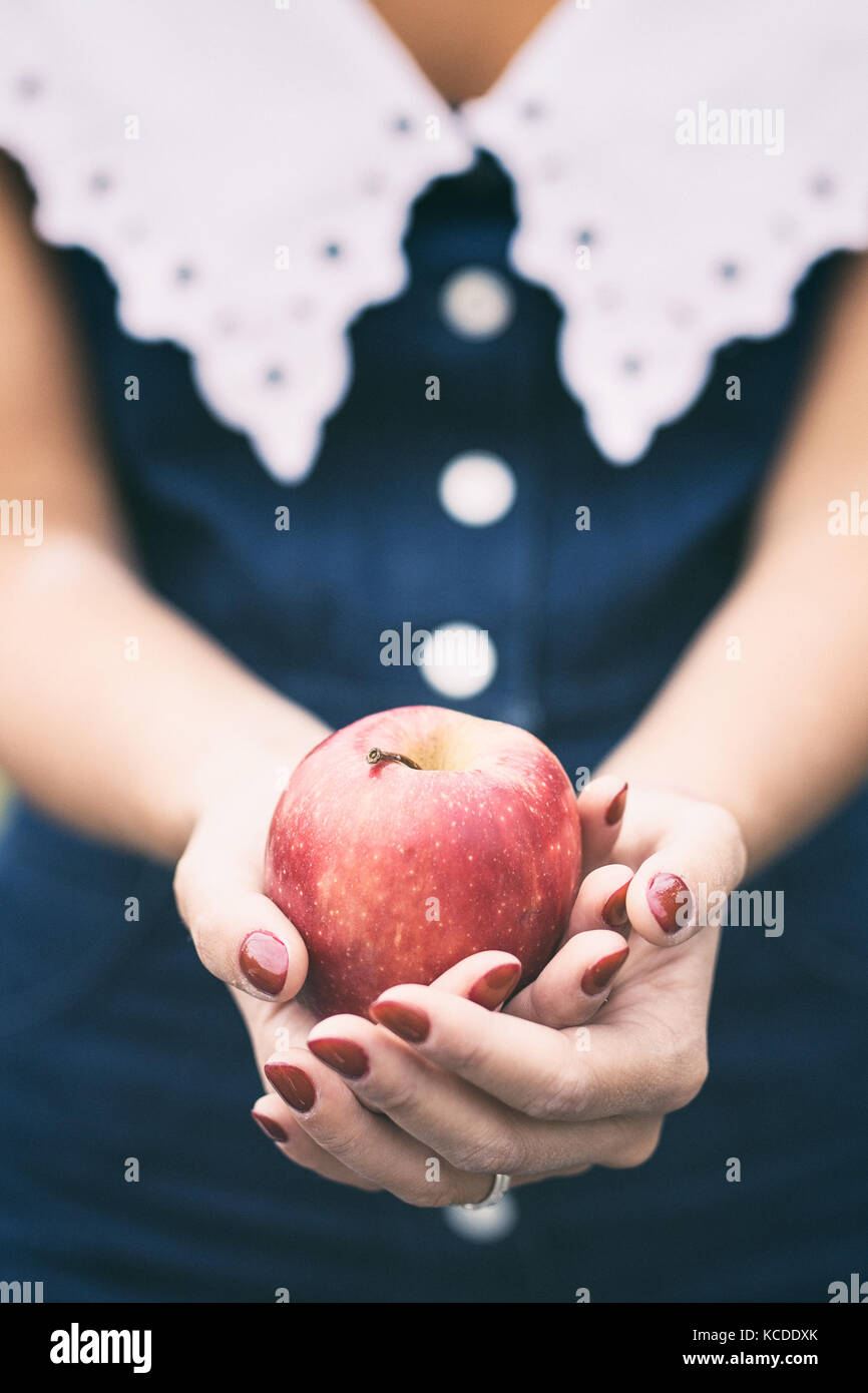 Hands of a girl holding a red apple - Stock Image