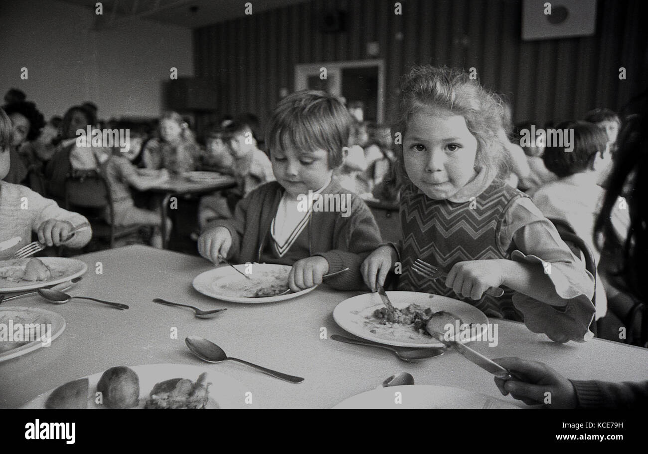 1970s, historical, two young girls eating their school dinner at Langbourne Primary School, Dulwich, London, England, - Stock Image