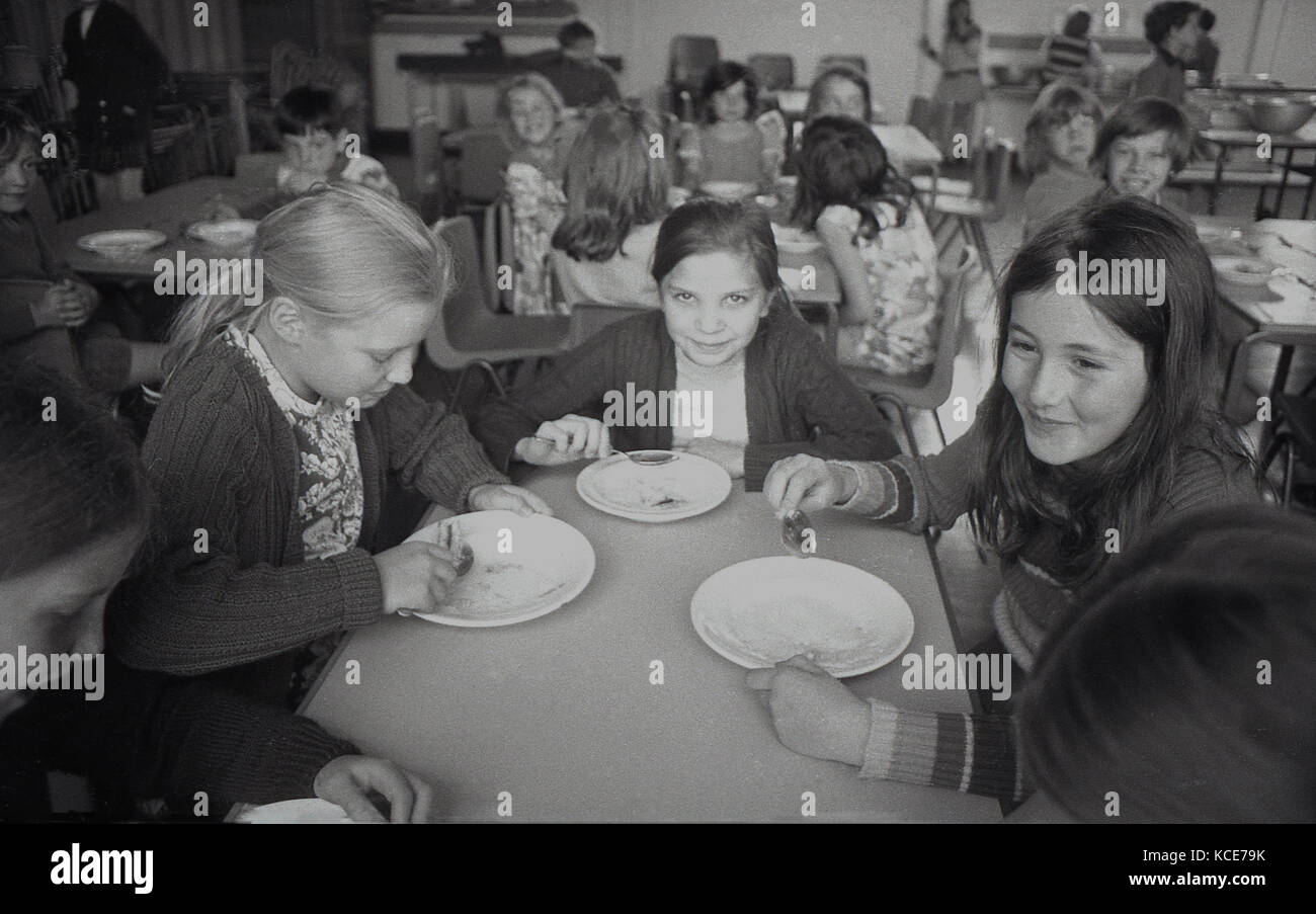 1970s, historical picture, three young girls sitting together enjoying the pudding of their school dinner, Langbourne - Stock Image