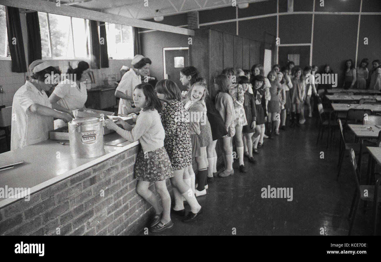 1970s, historical picture showing youngl girls at Langbourne Primary School queuing up inside for their school dinner - Stock Image