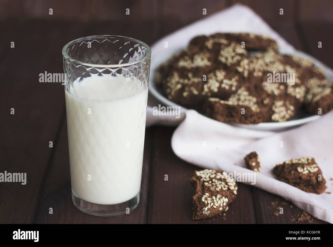 Chocolate cookies with sesame seeds in a vintage plate and a glass of milk on wooden background - Stock Image