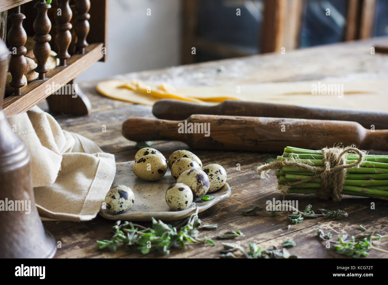 Ingredients for making homemade pasta, rolling pin, quail eggs, asparagus on wooden table - Stock Image