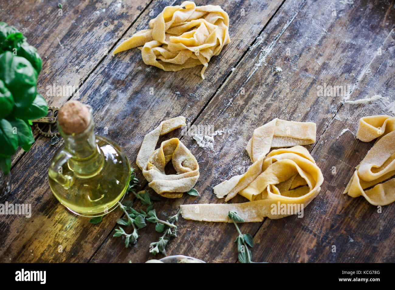 Raw homemade pasta on wooden table - Stock Image