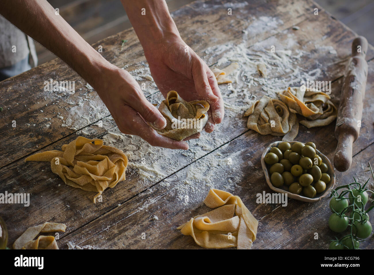 The young man in apron making homemade pasta - Stock Image