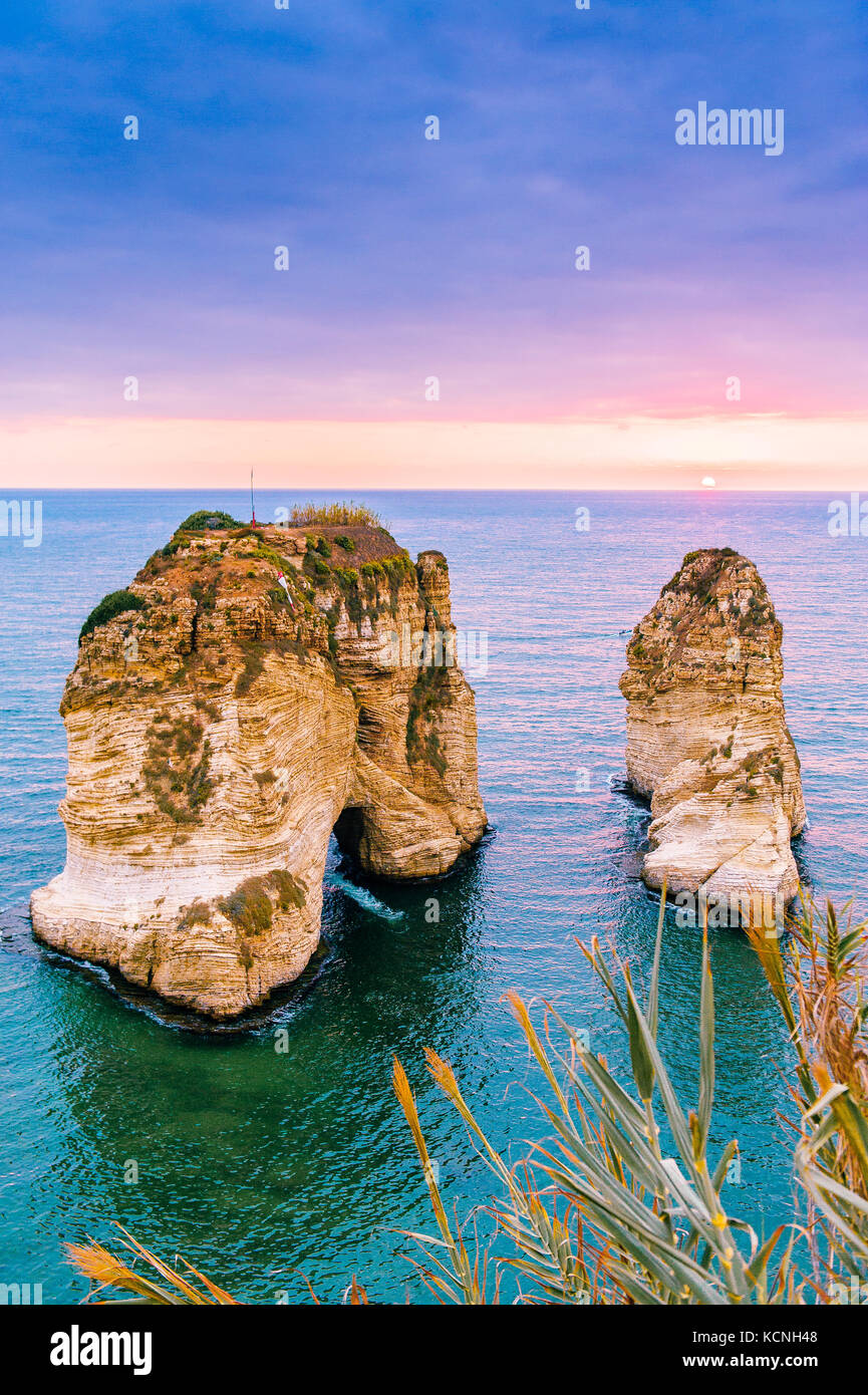Beautiful sunset on Raouche, Pigeons' Rock. In Beirut, Lebanon.Sun and Stones are reflected in water.dense clouds - Stock Image