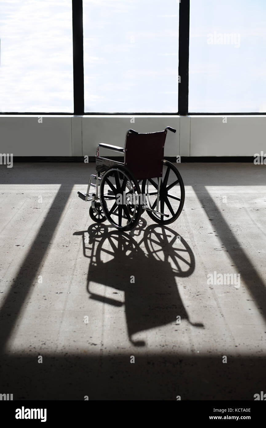 a-single-empty-wheelchair-in-a-building-with-a-concrete-floor-KCTA0E.jpg