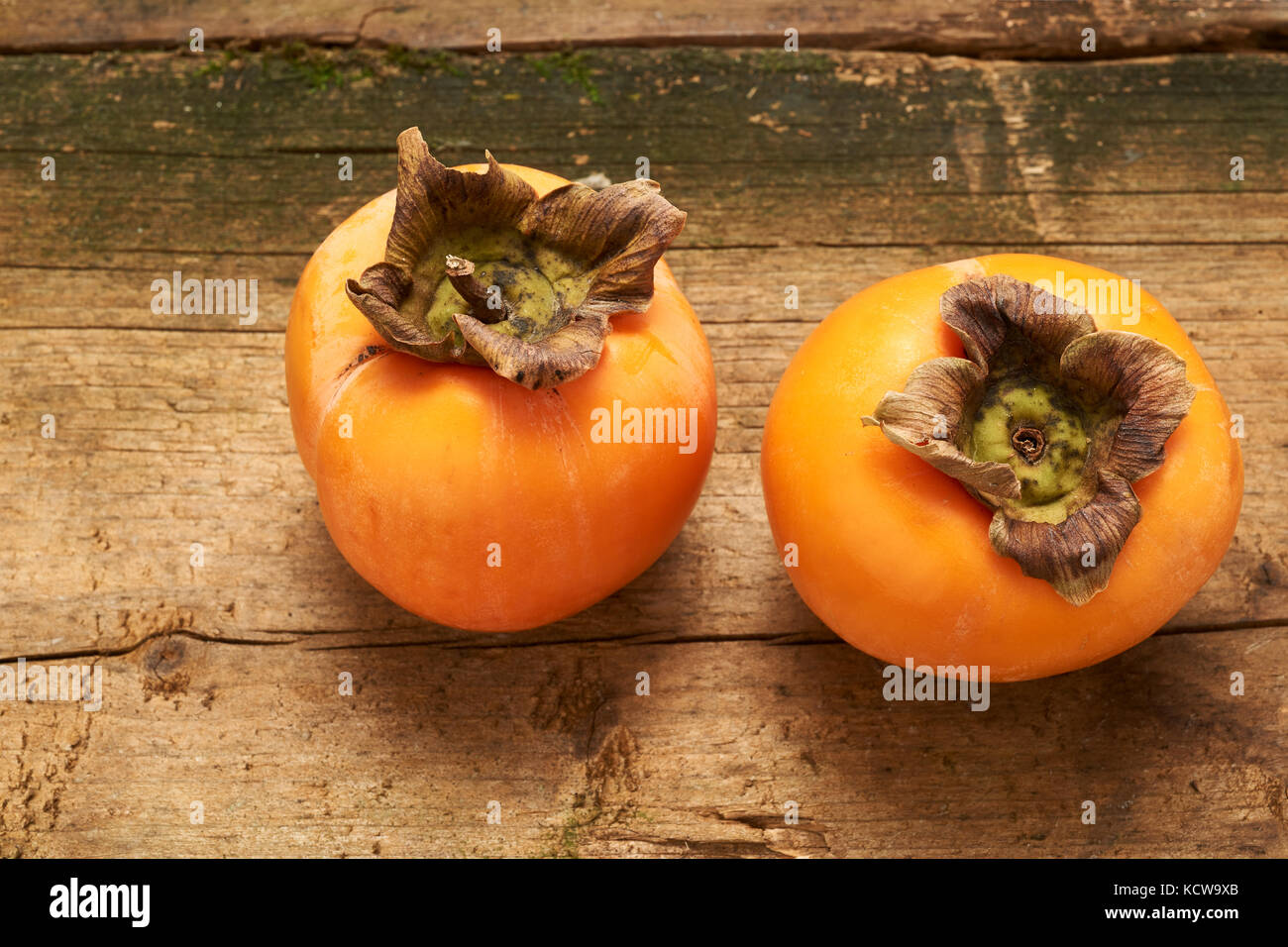 two delicious orange persimmon on an old wooden table - Stock Image
