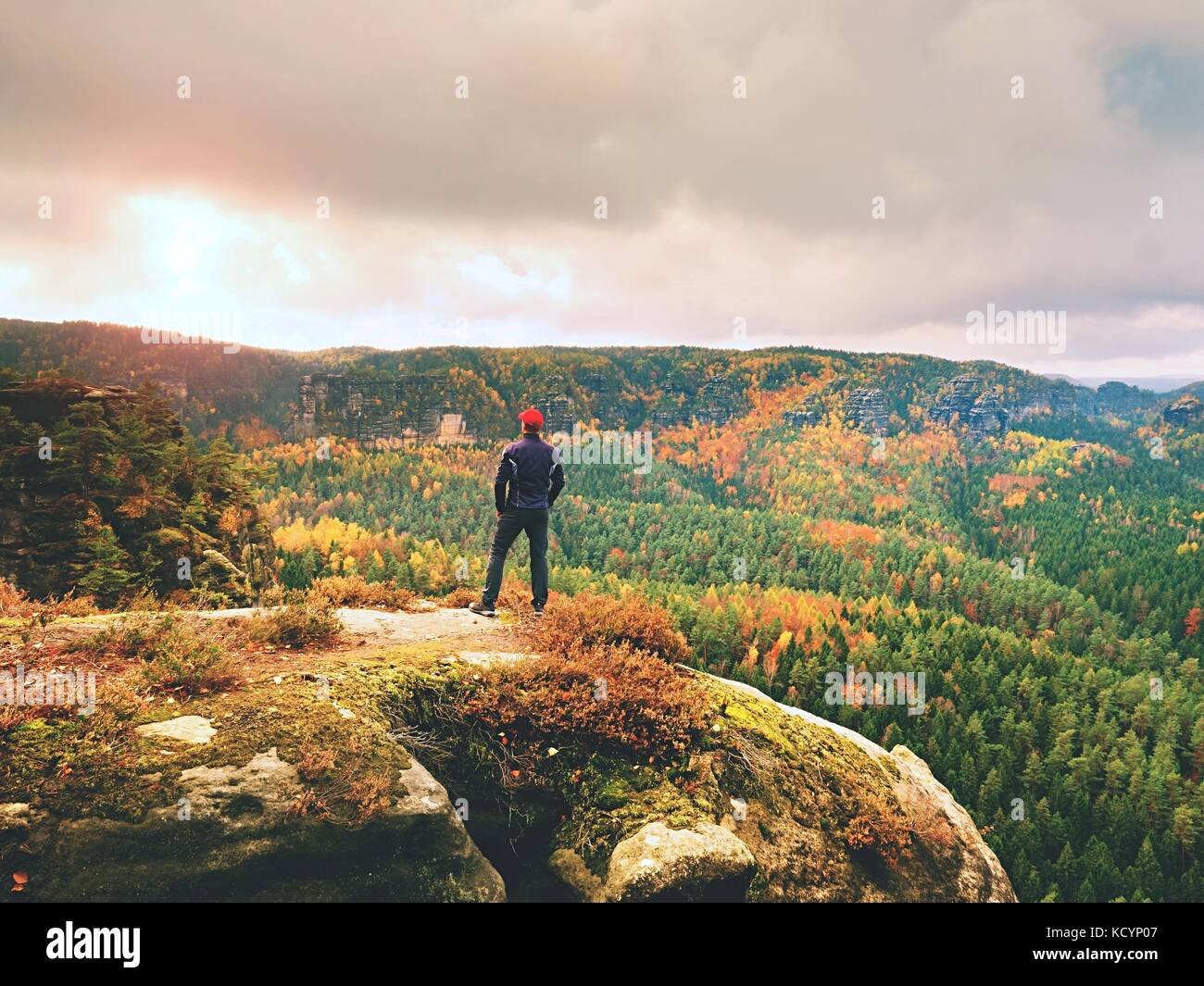 Alone tourist with outdoor sportswear and backpack stand on cliff edge  and watching into colorful autumn valley - Stock Image