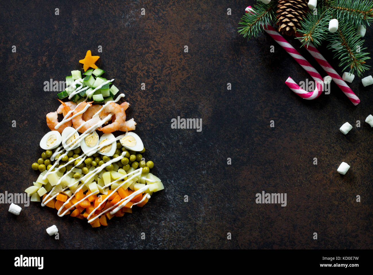 Christmas tree from a salad olivier on a brown rusty stone or metal background. Top view with a copy. - Stock Image