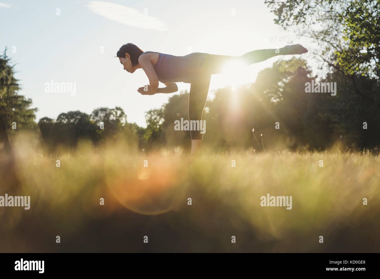Mature woman in park, balancing on one leg, in yoga position, low angle view - Stock Image