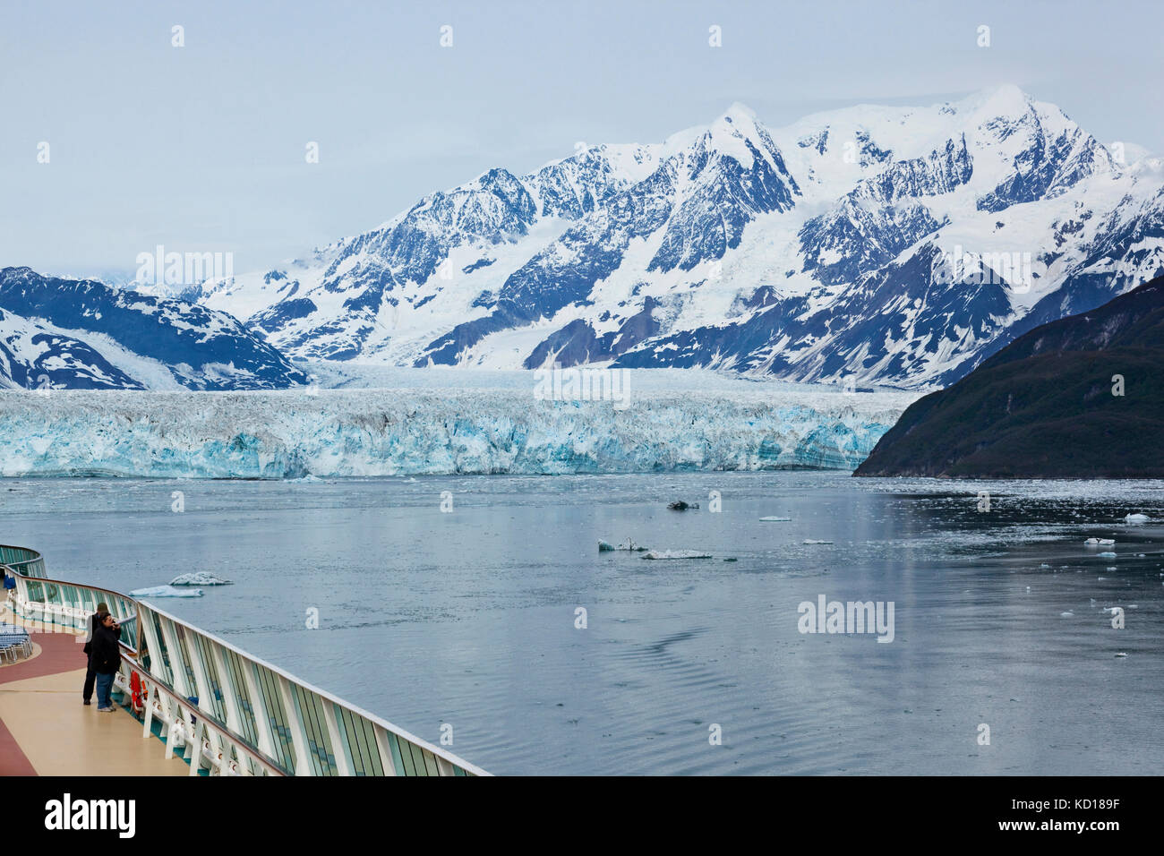 Couple on the deck of a cruise ship taking photos of Hubbard Glacier and surrounding area. Disenchantment Bay, Alaska, Stock Photo