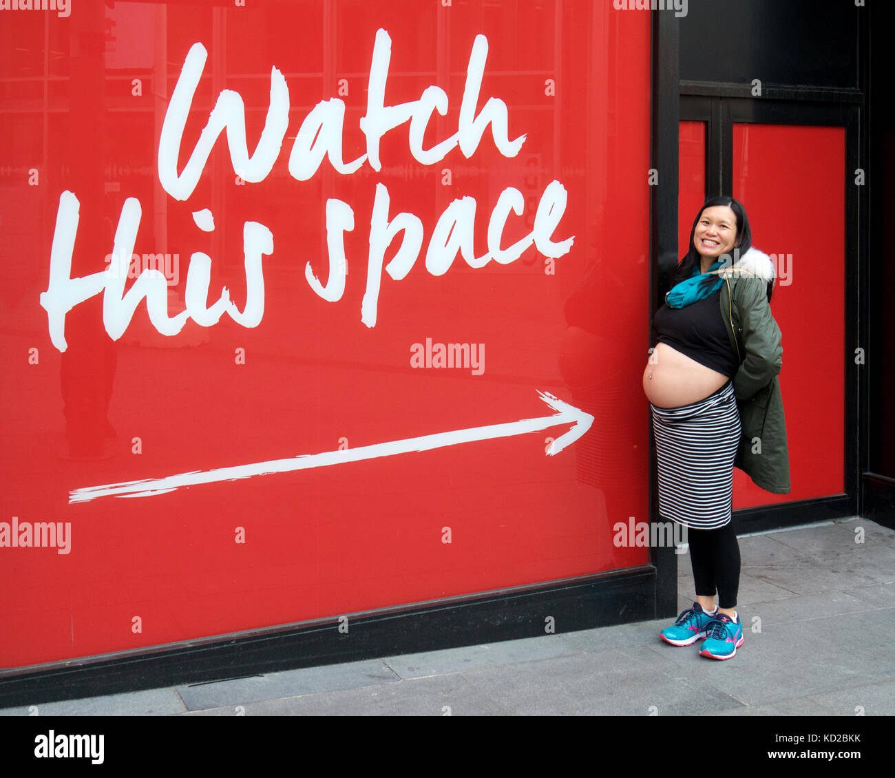 Pregnant Chinese woman standing next to  'Watch This Space' sign - Stock Image