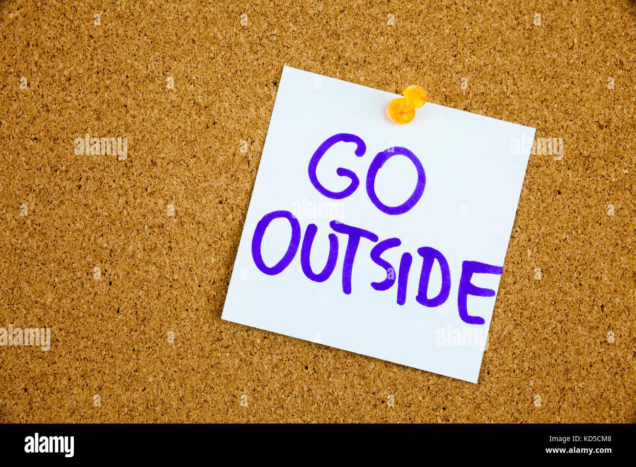 A yellow sticky note writing, caption, inscription go outside, enjoy life, motivational lifestyle reminders on colorful - Stock Image