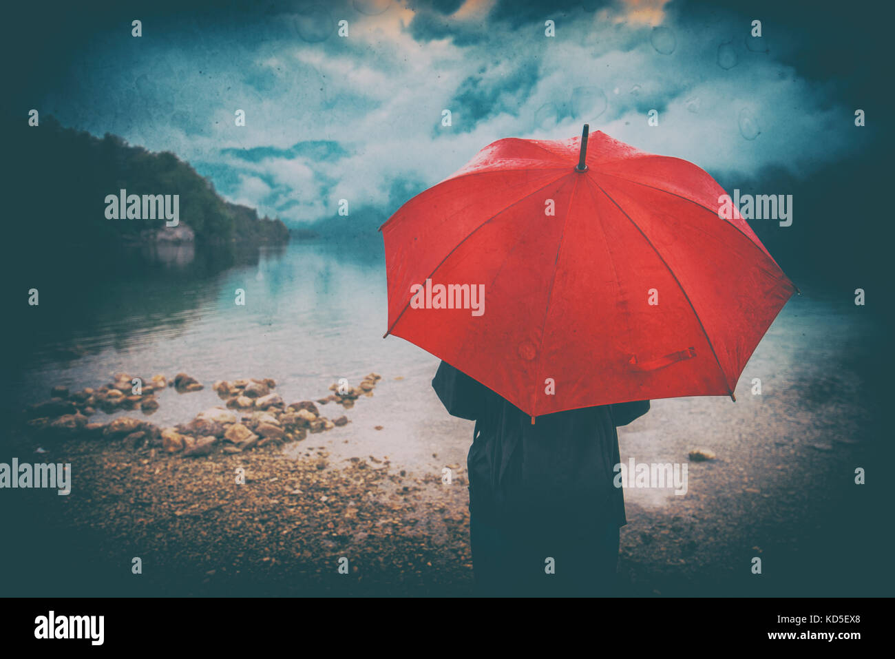 Woman with red umbrella contemplates on rain in front of a lake. Sad and lonely female person looking into distance. - Stock Image