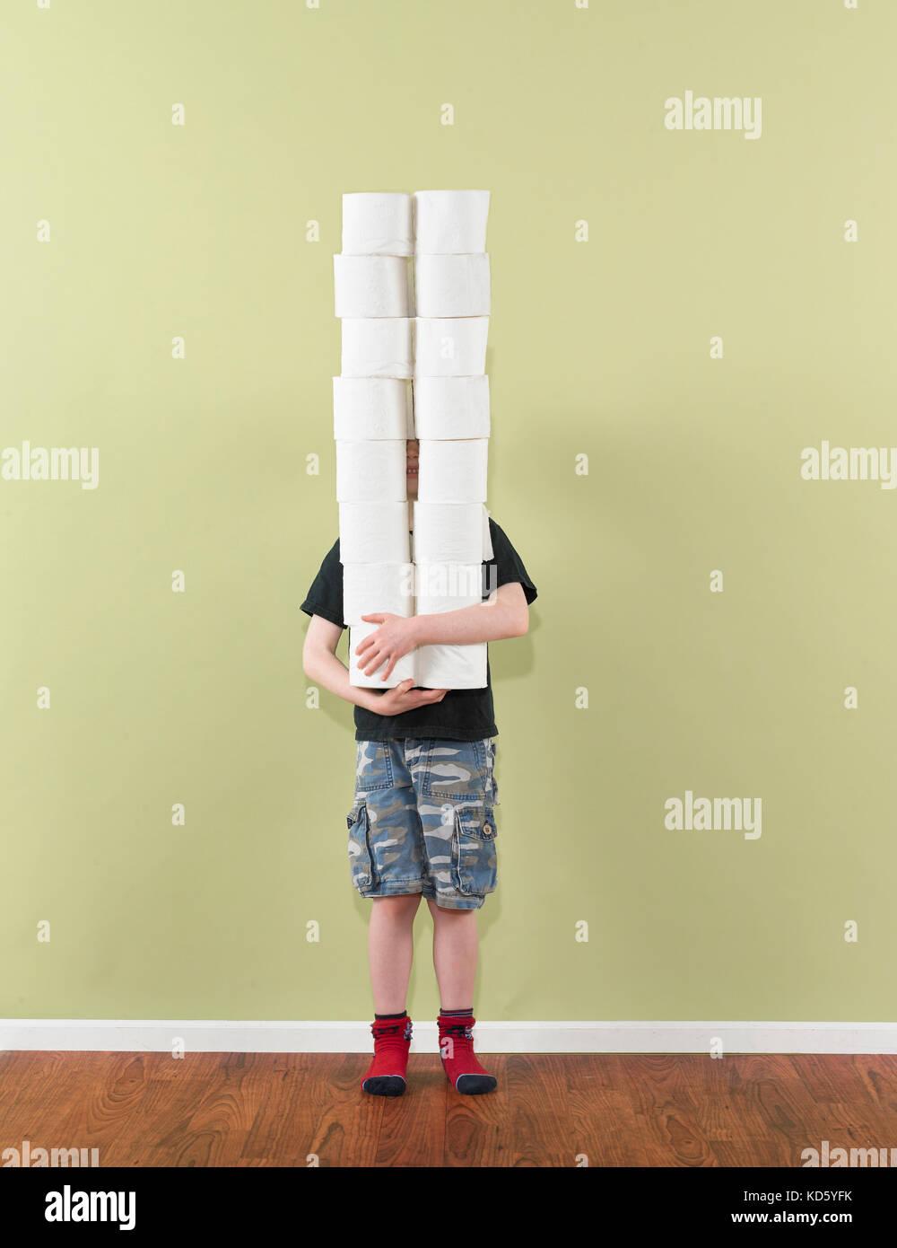 boy 4-7 balancing two stacks of toilet paper - Stock Image