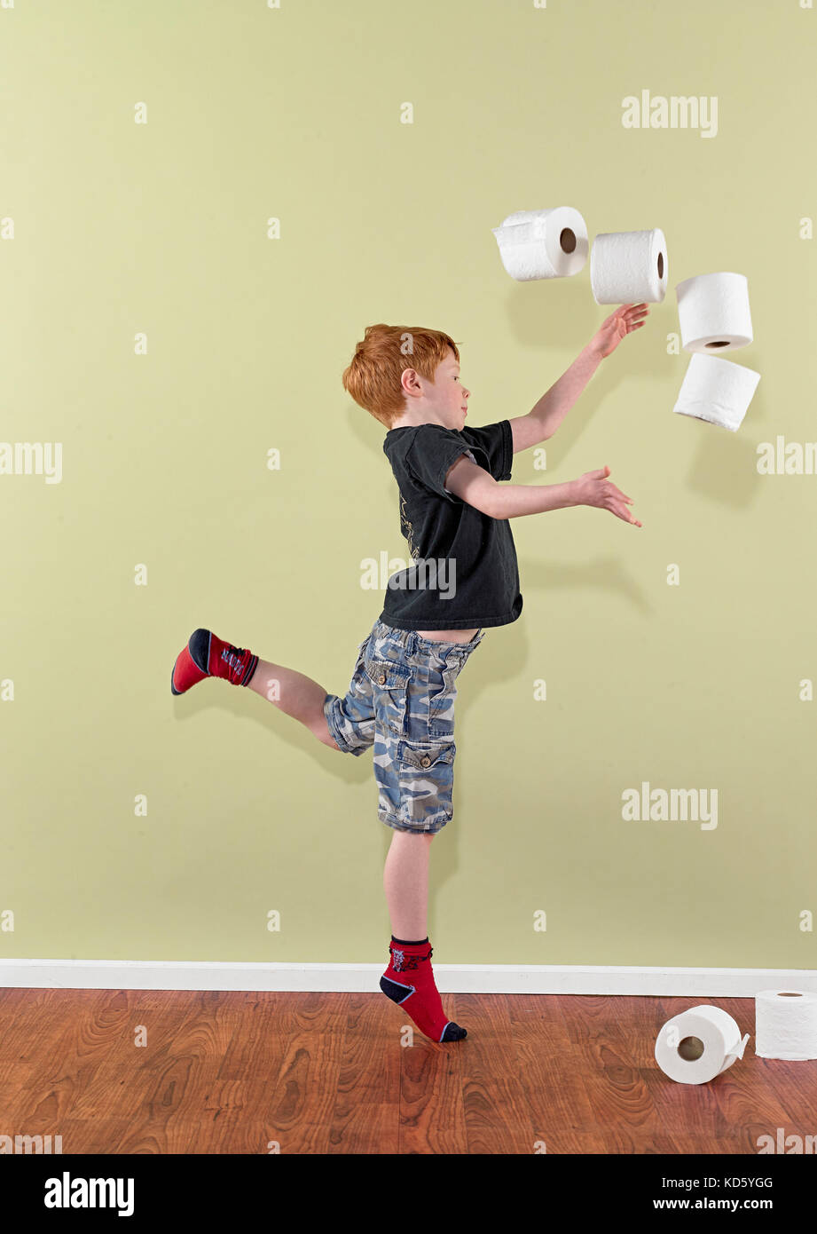 Boy 4-7 throwing rolls of toilet paper - Stock Image