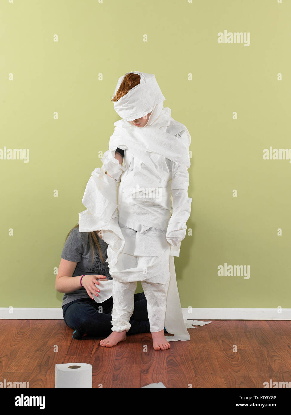 Teen girl wrapping boy in toilet paper - Stock Image