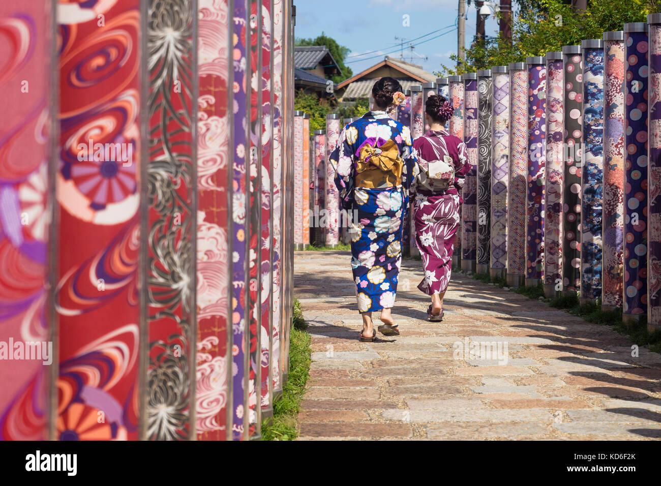 Arashiyama, Kyoto, Japan - September 18 2017: Two woman with kimonos walk through poles with traditional colourful - Stock Image