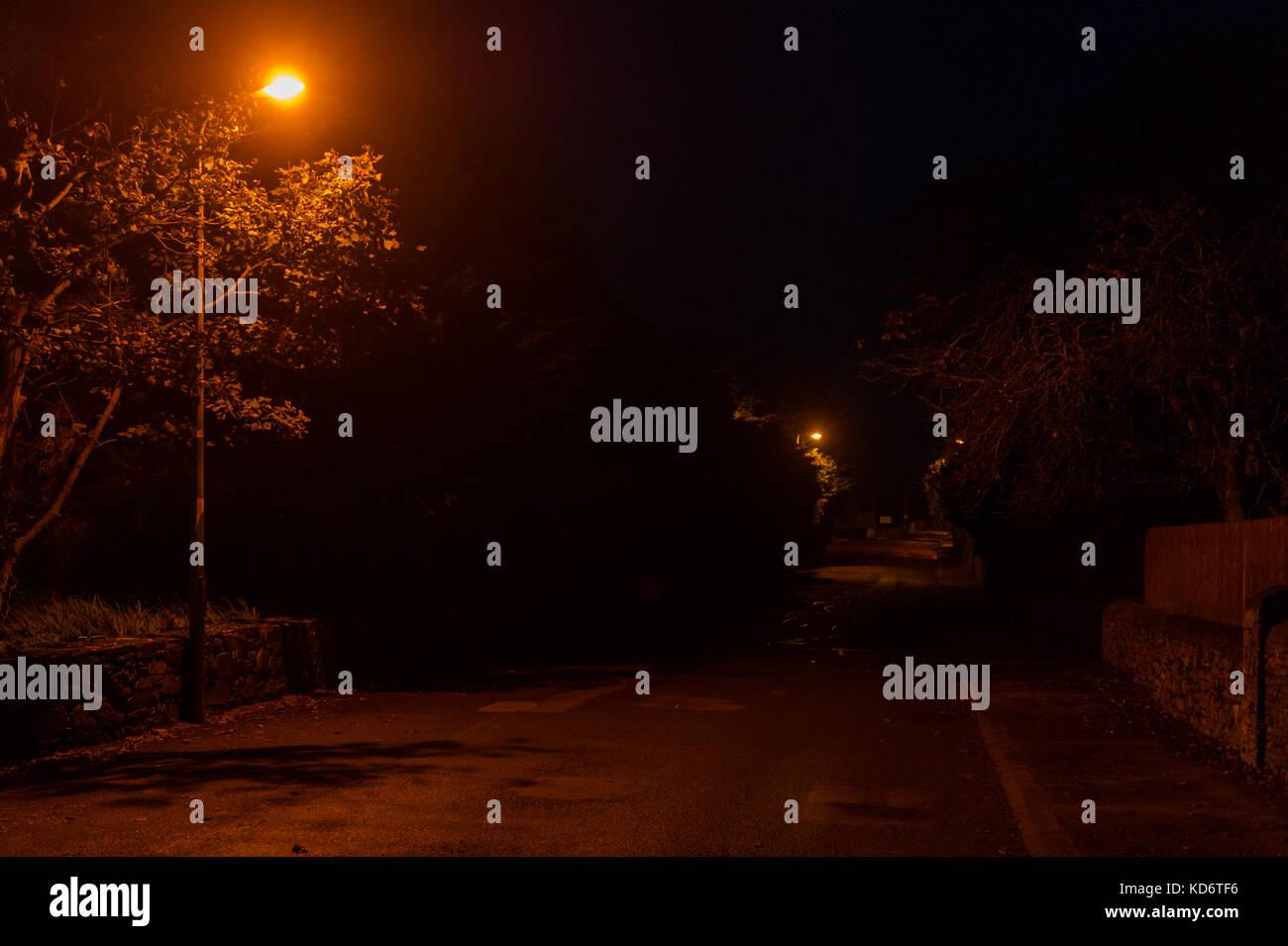 empty-road-on-a-dark-night-with-an-orange-street-light-illuminating-KD6TF6.jpg