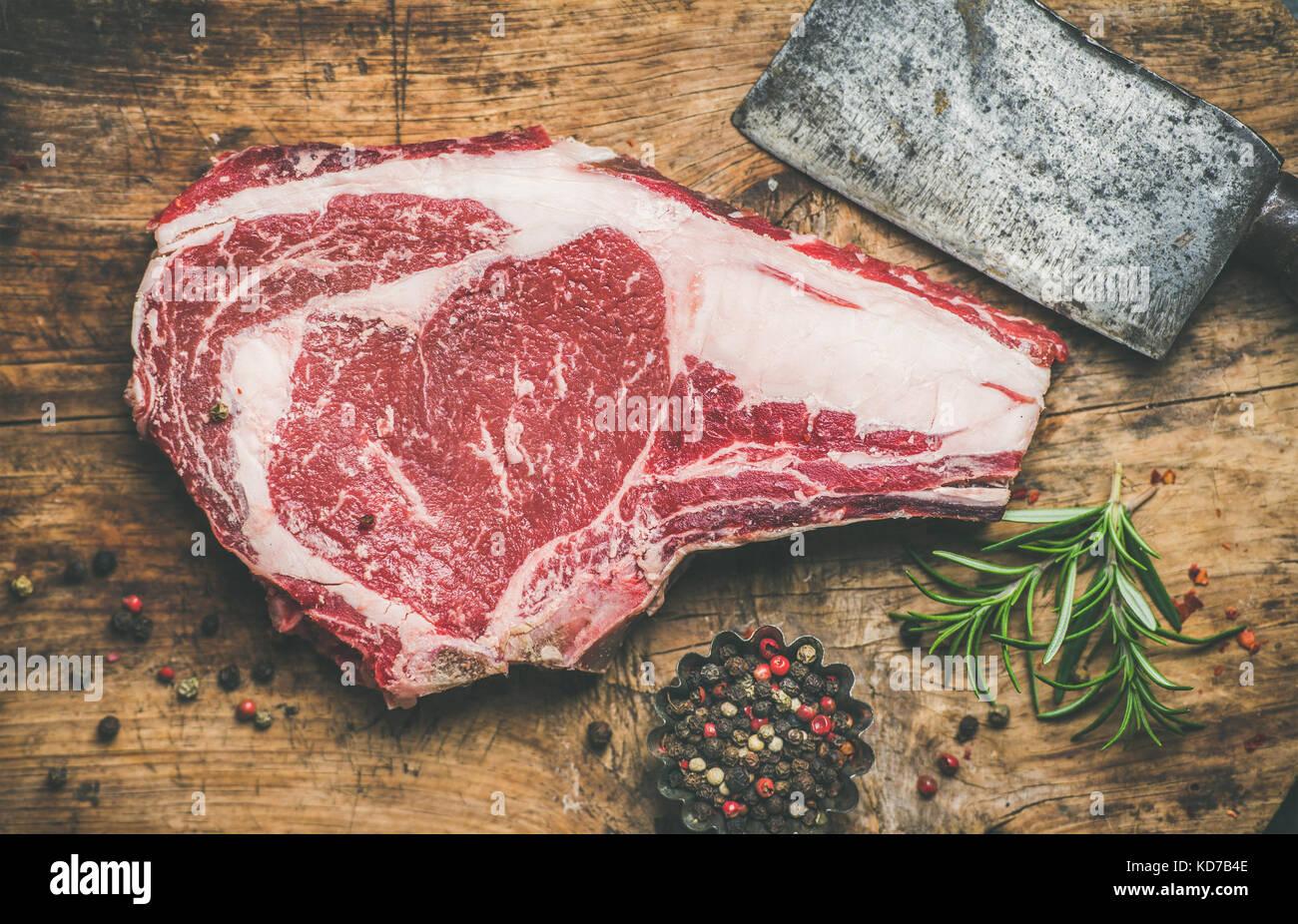 Raw beef steak rib-eye with seasoning and knife, rustic background - Stock Image