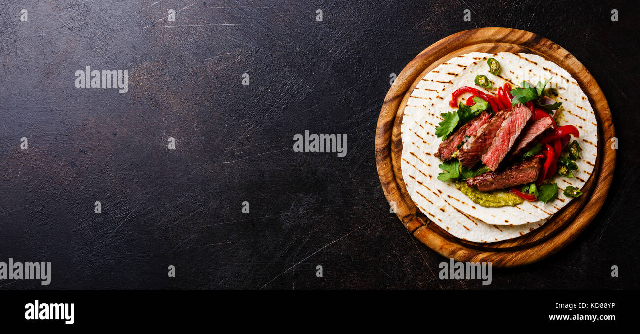 Grilled Beef steak Fajitas taco tortillas with green salsa and bell pepper on dark background copy space - Stock Image