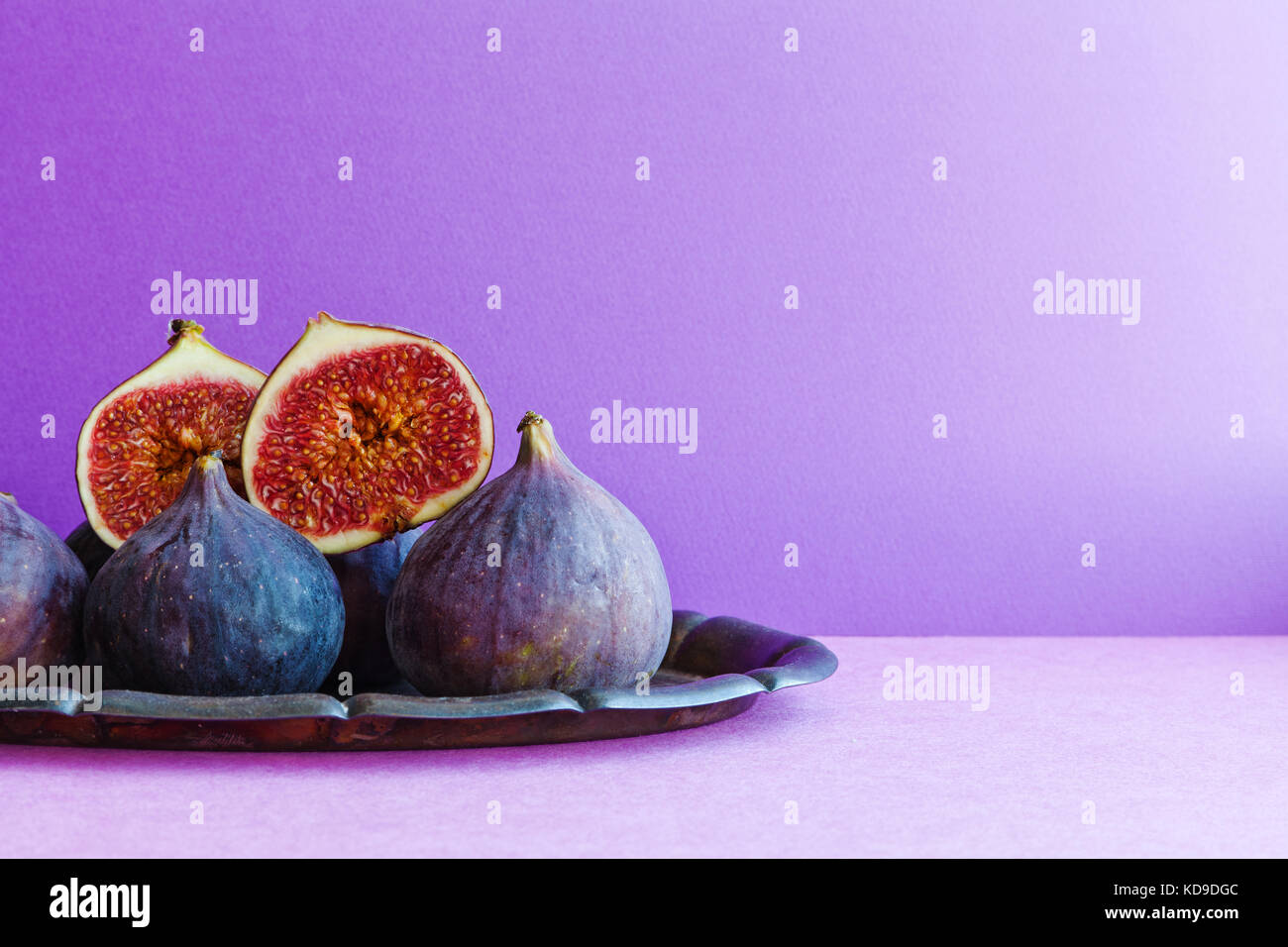 Bright still life organic fig fruits on an old tray, beautiful purple violet background. Selective focus photography, - Stock Image