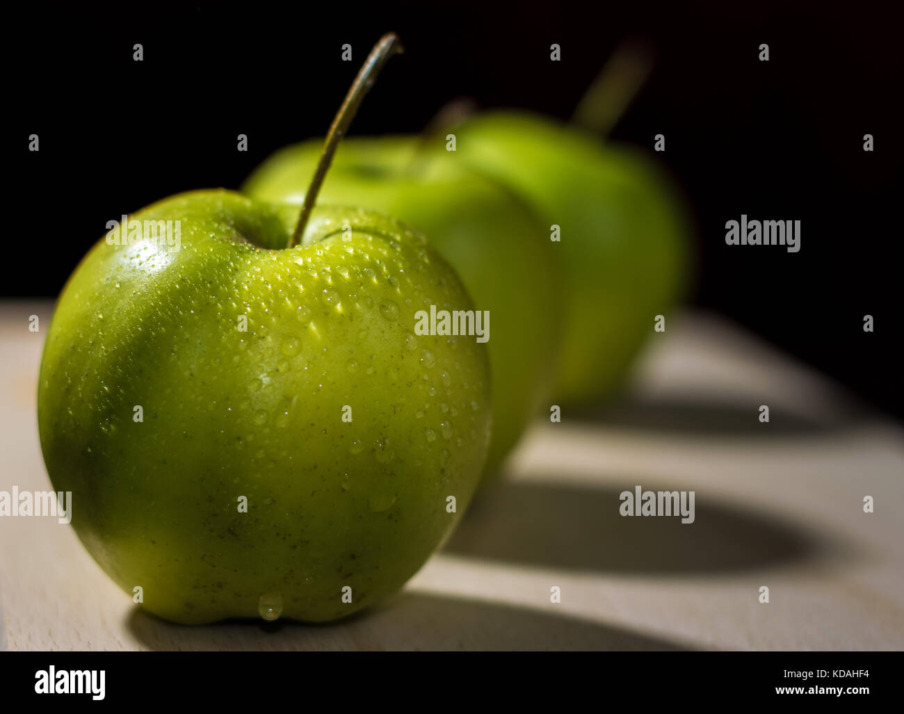 Three apples arranged in a diagonal line on a wooden surface with dark background - Stock Image