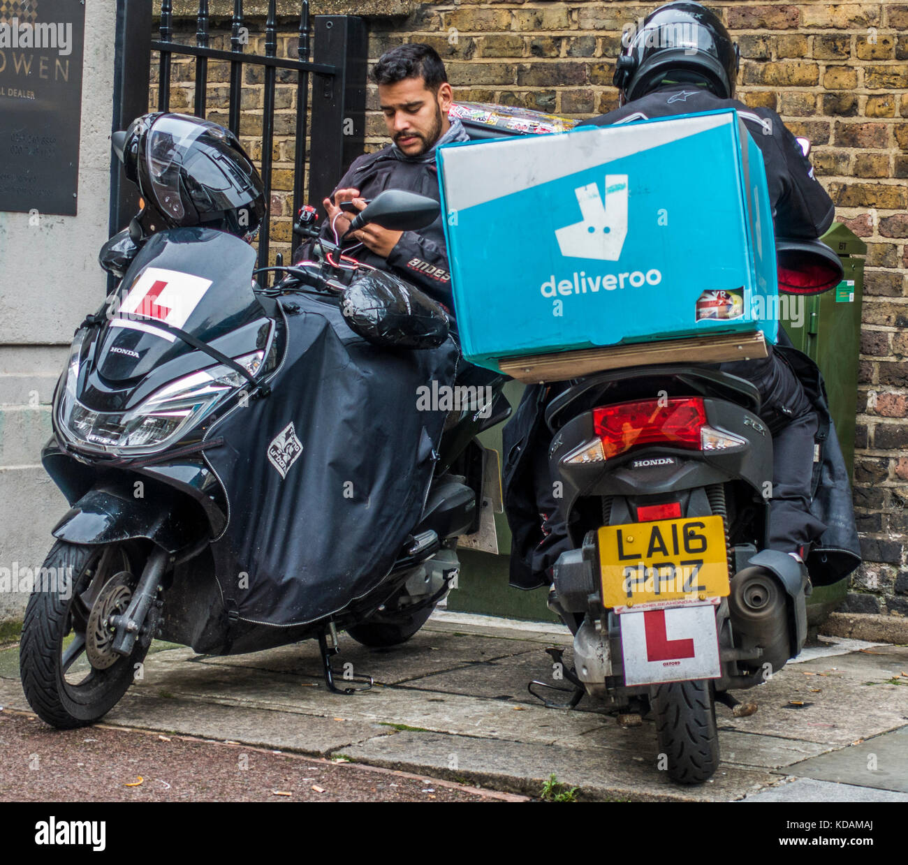 Two male deliveroo (online food delivery company) motorbike riders, taking a break from delivering orders in London, - Stock Image
