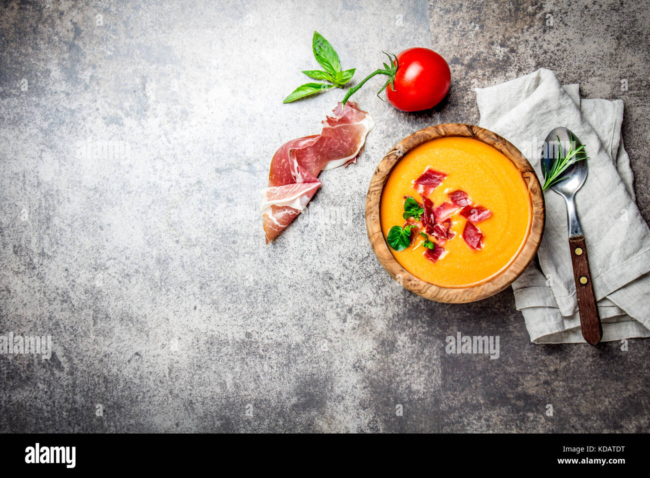 Spanish tomato soup Salmorejo served in olive wooden bowl with ham jamon serrano on stone background. Top view, - Stock Image