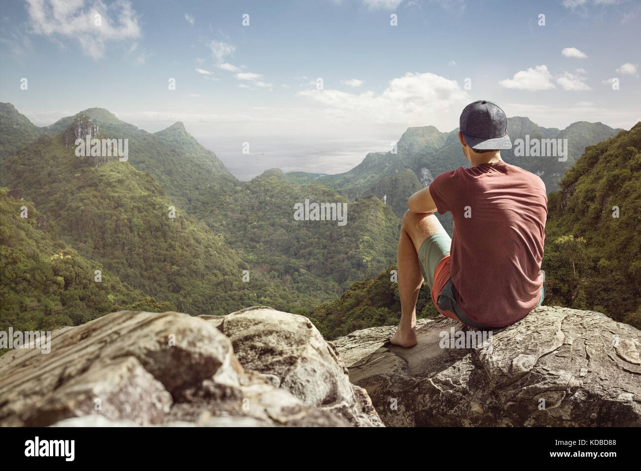 Young man has a panoramic view on a tropical landscape - Stock Image