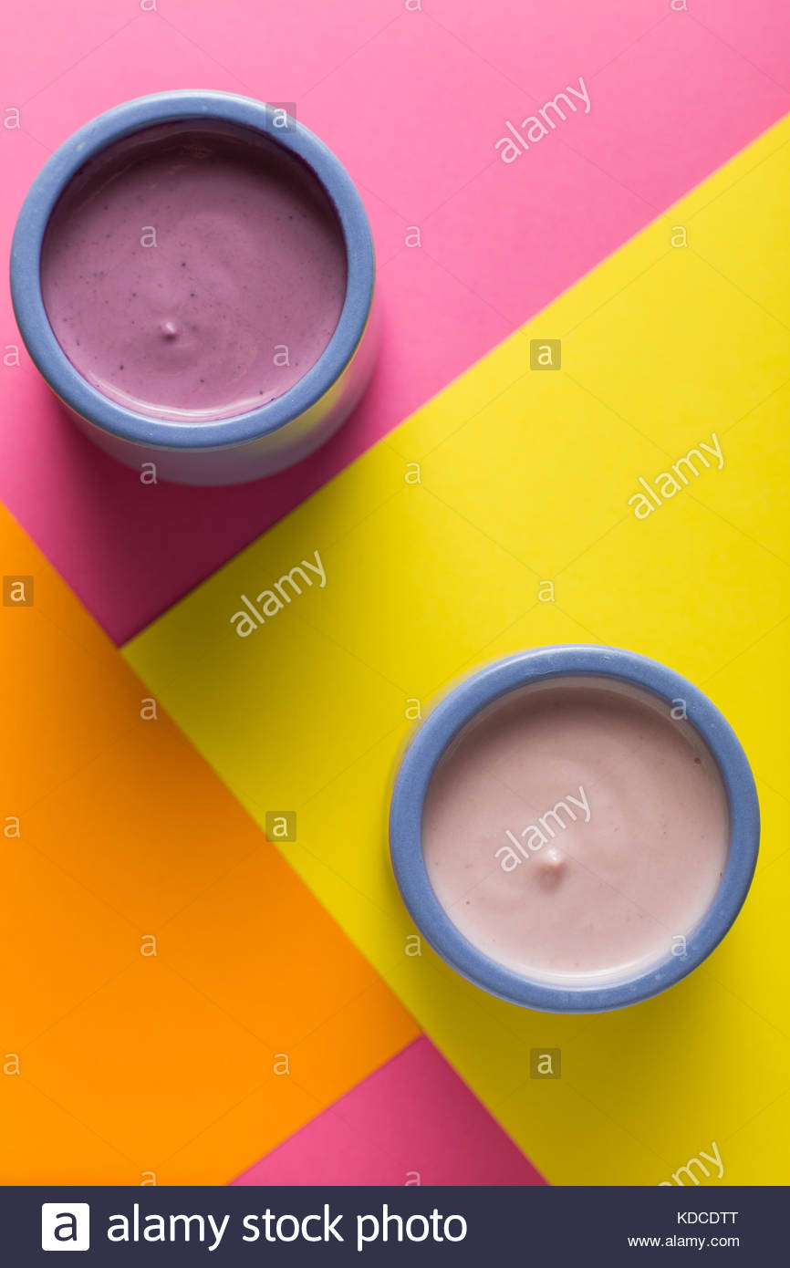 Yogurts assortment in ceramic bowls on colorful background. Natural and fruit healthy, diet, gourmet dessert for - Stock Image