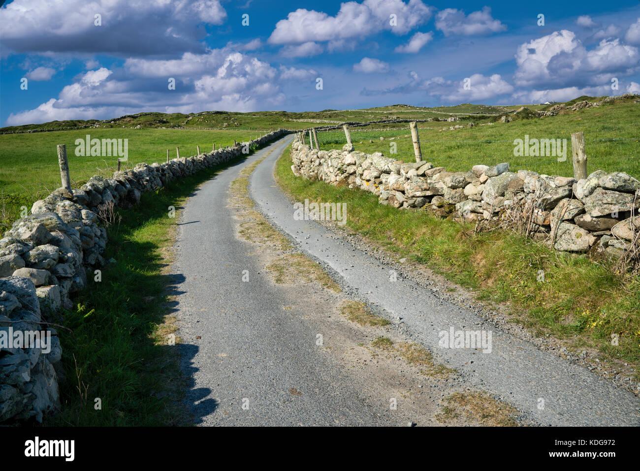 couple walking on road on Omey Island. Connemara,County Galway,Ireland - Stock Image