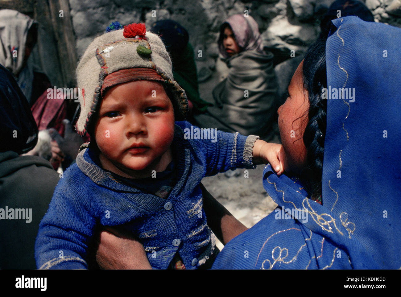 Upper Indus Valley Pakistan, 1990; A young girl holds her baby brother at a  gathering in Shigar village. - Stock Image
