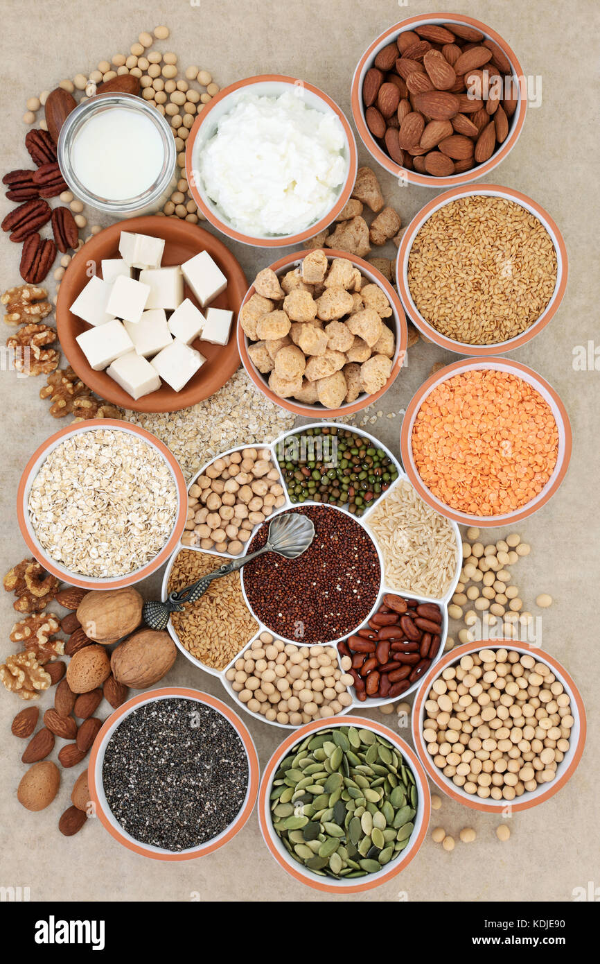 Health food for vegans with tofu, legumes, nuts, seeds, cereals, soya yoghurt, milk and chunks with foods high in - Stock Image