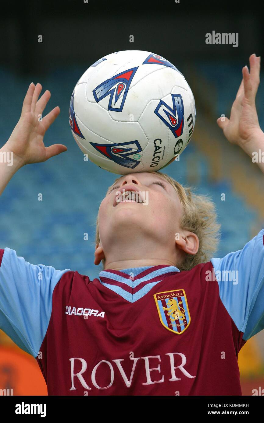 A young boy in an Aston Villa soccer shirt balances a football on his head Stock Photo