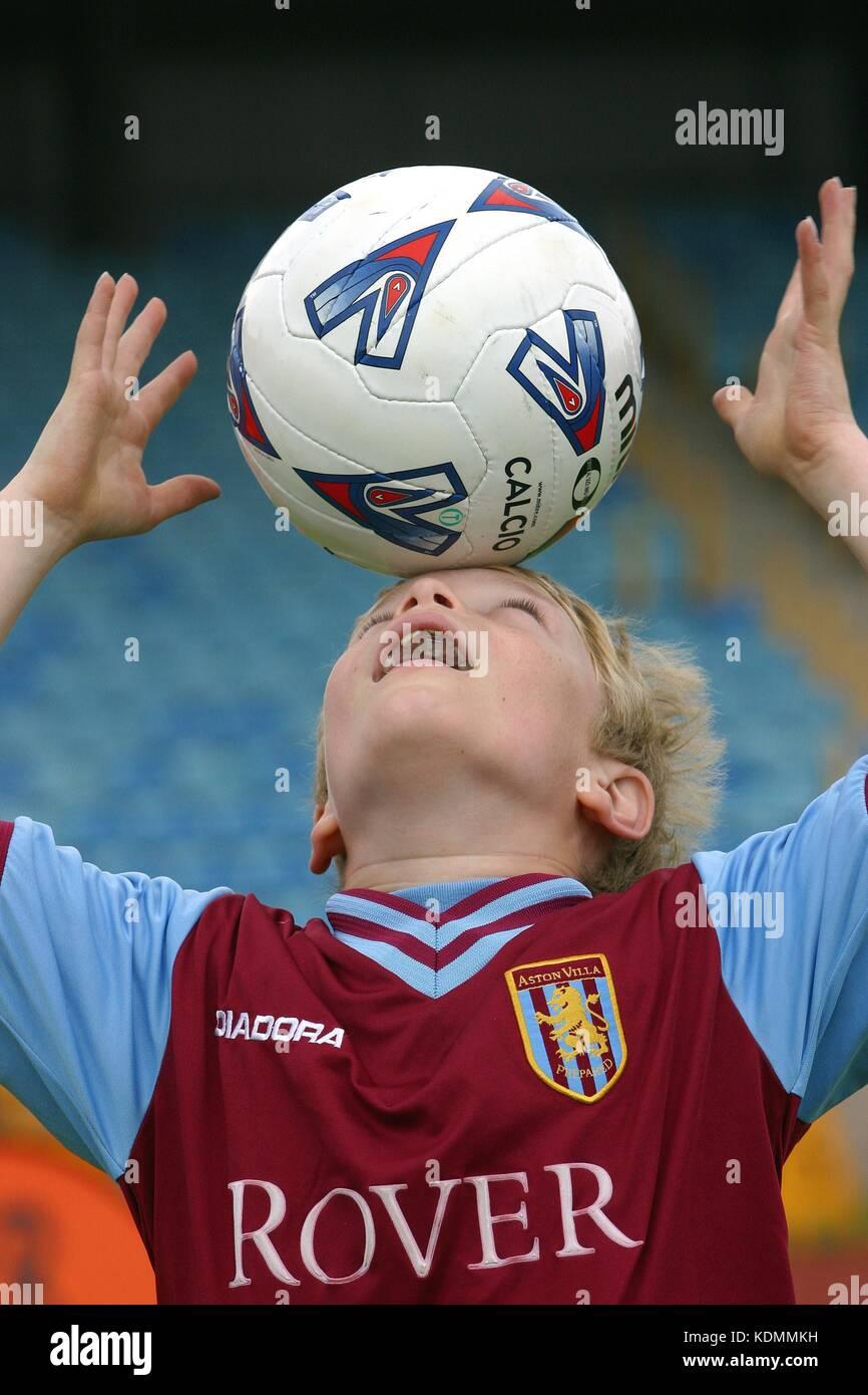 A young boy in an Aston Villa soccer shirt balances a football on his head Stock Photo
