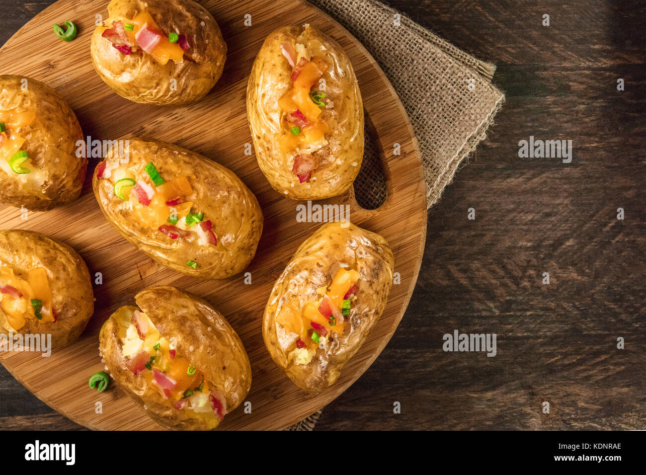Baked potatoes with cheese, bacon, and copy space - Stock Image