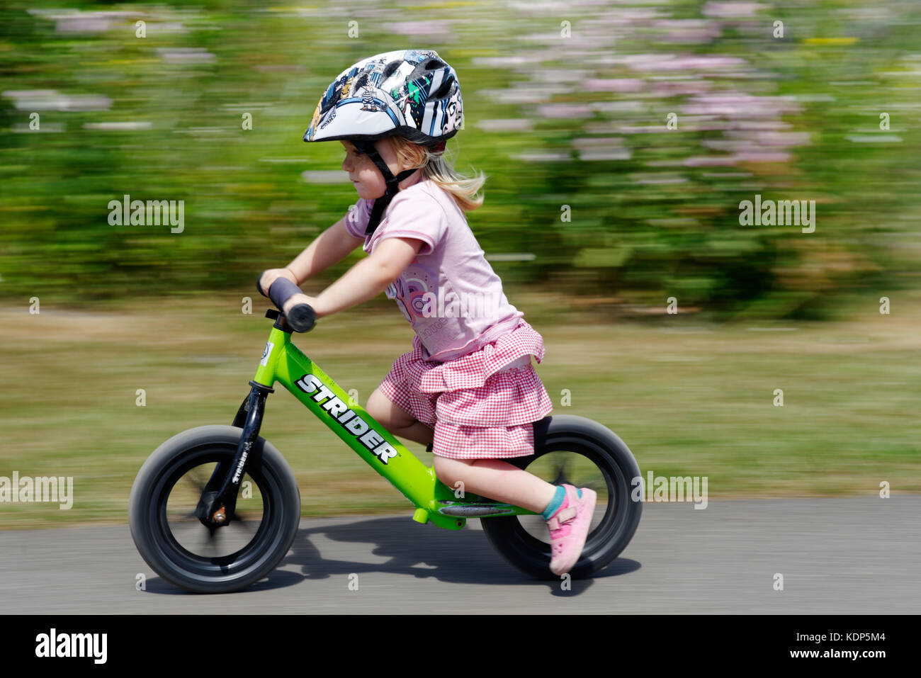 a-three-year-old-girl-riding-a-balance-bike-KDP5M4.jpg