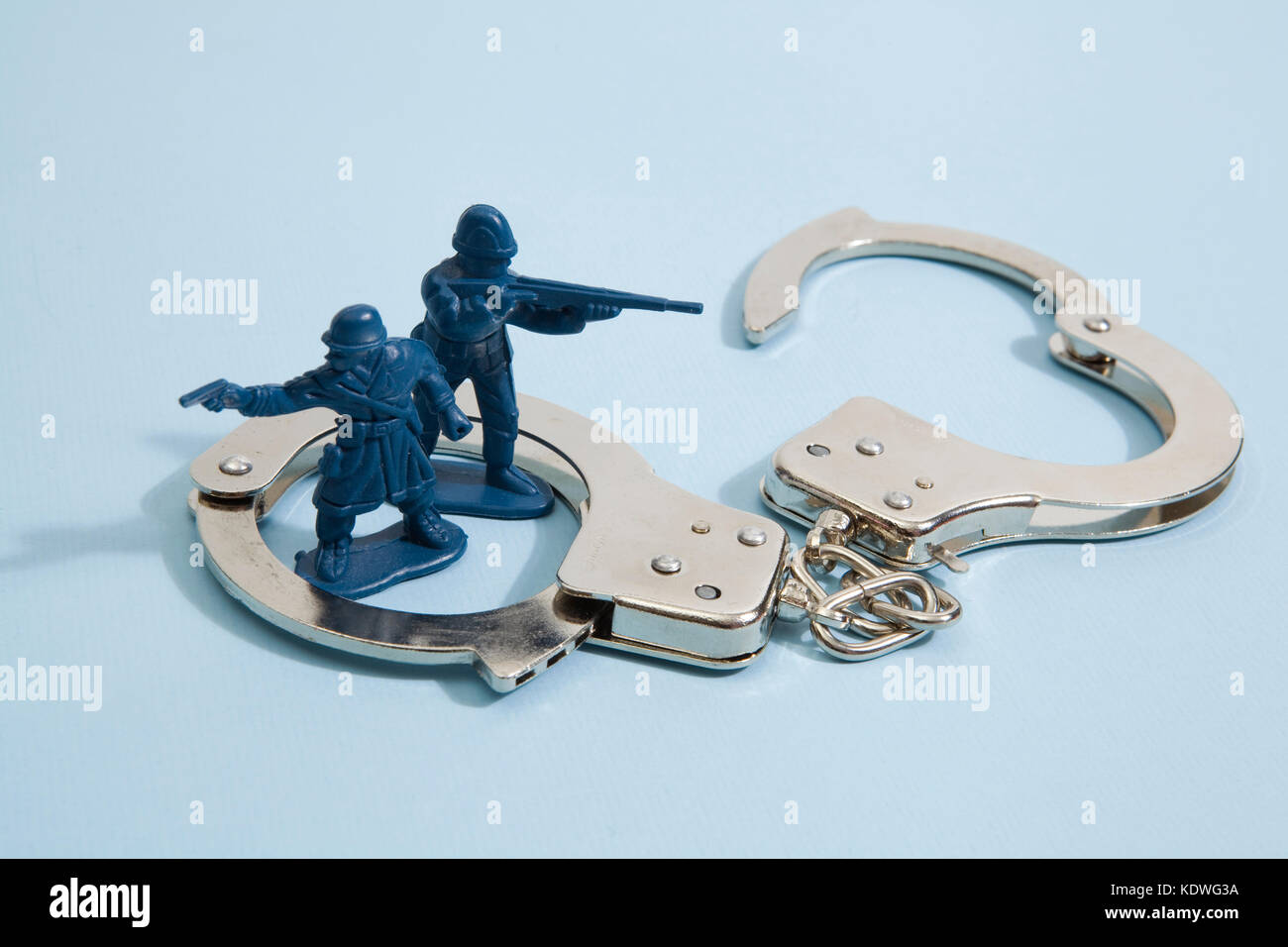 isolated handcuffs besieged plastic toy soldiers on a pop vibrant blue color background. Minimal color still life - Stock Image