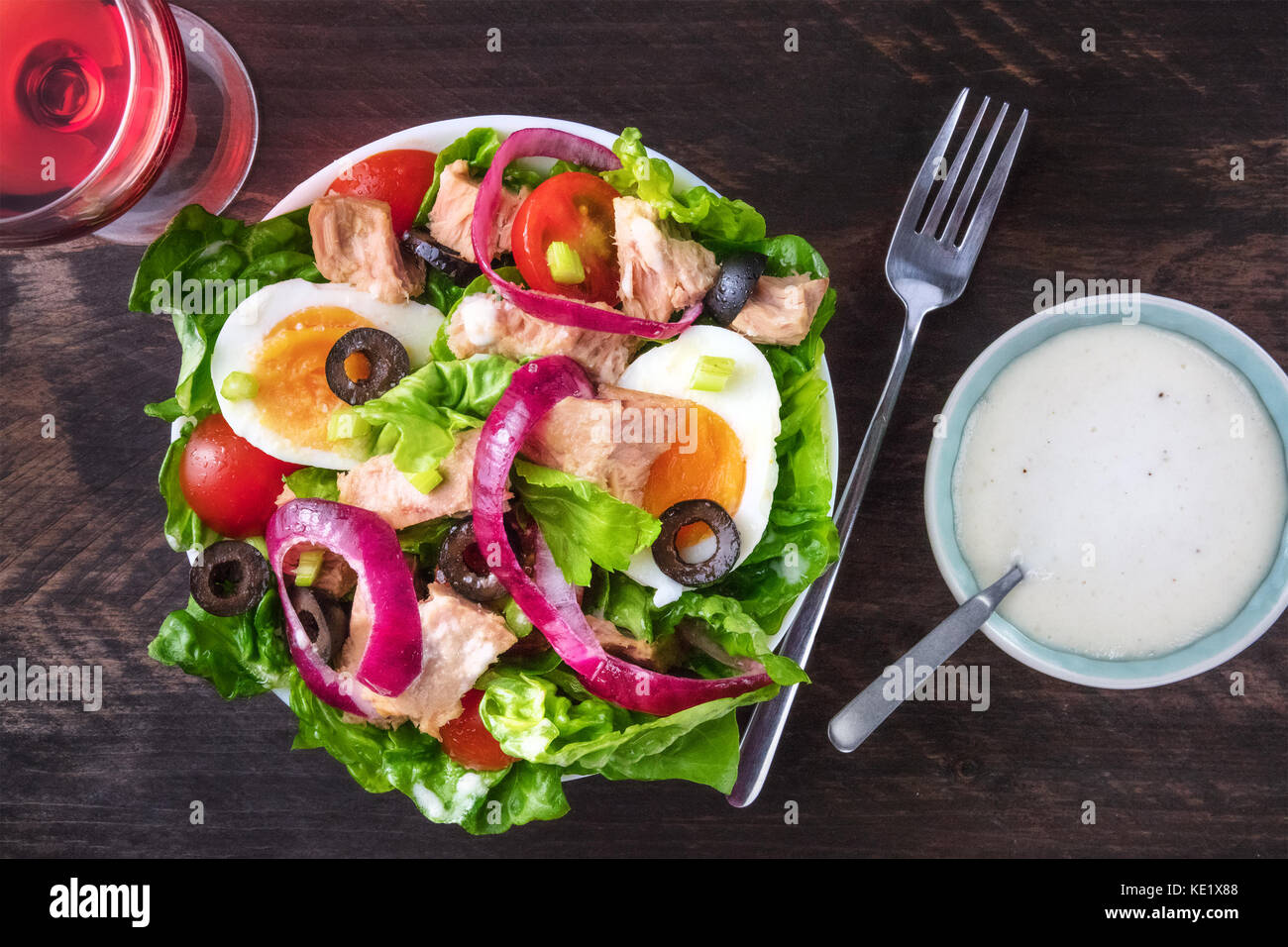 Overhead photo of tuna salad with rose wine, fork, sauce - Stock Image