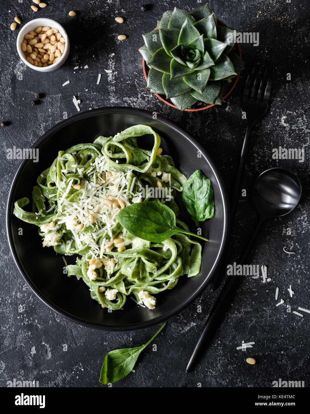 Green spinach pasta with cheese and pine nuts in a black bowl with black cutlery. Gourmet italian meal. Top view - Stock Image