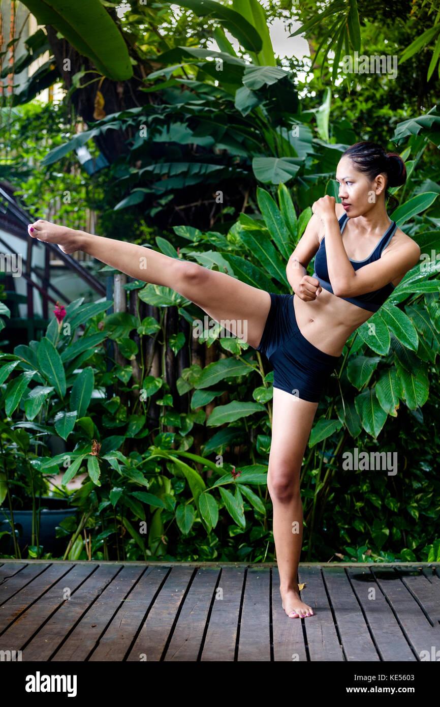 Young Asian woman practicing kick boxing - Stock Image