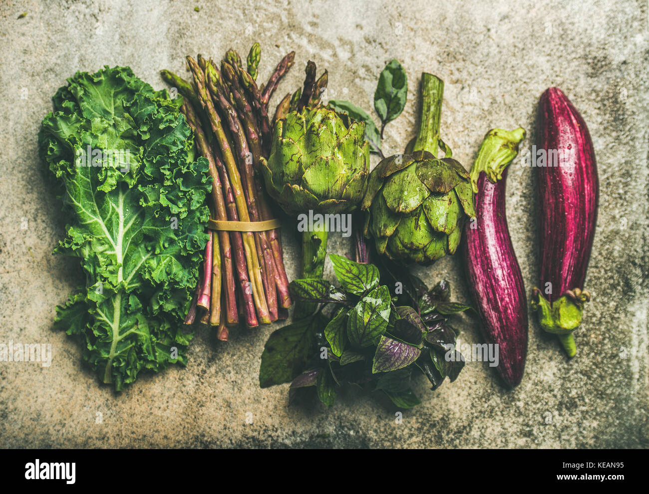 Flat-lay of fresh green and purple vegetables, top view - Stock Image