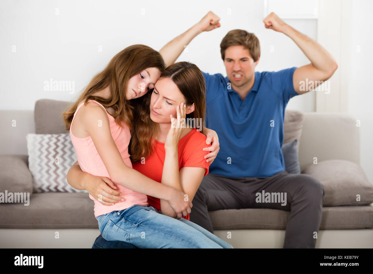 Depressed Mother And Daughter In Front Of Violent Father Sitting On Sofa - Stock Image