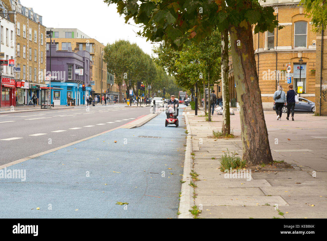 Man on mobility scooter in cycle lane on Mile End Road in London England Stock Photo