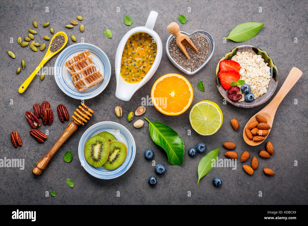 Ingredients for the healthy foods background Mixed nuts, honey, berries, fruits, blueberry, orange, almonds, oatmeal - Stock Image