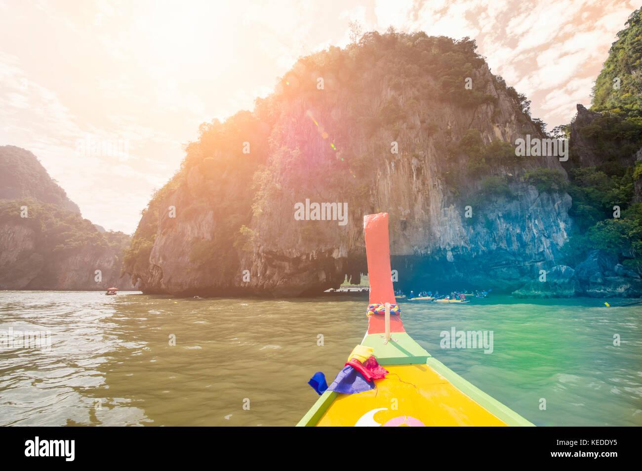 A long tail boat is sailing in the Ao Phang Nga (Phang Nga Bay) National Park at sunset. Phang Nga is one of the - Stock Image