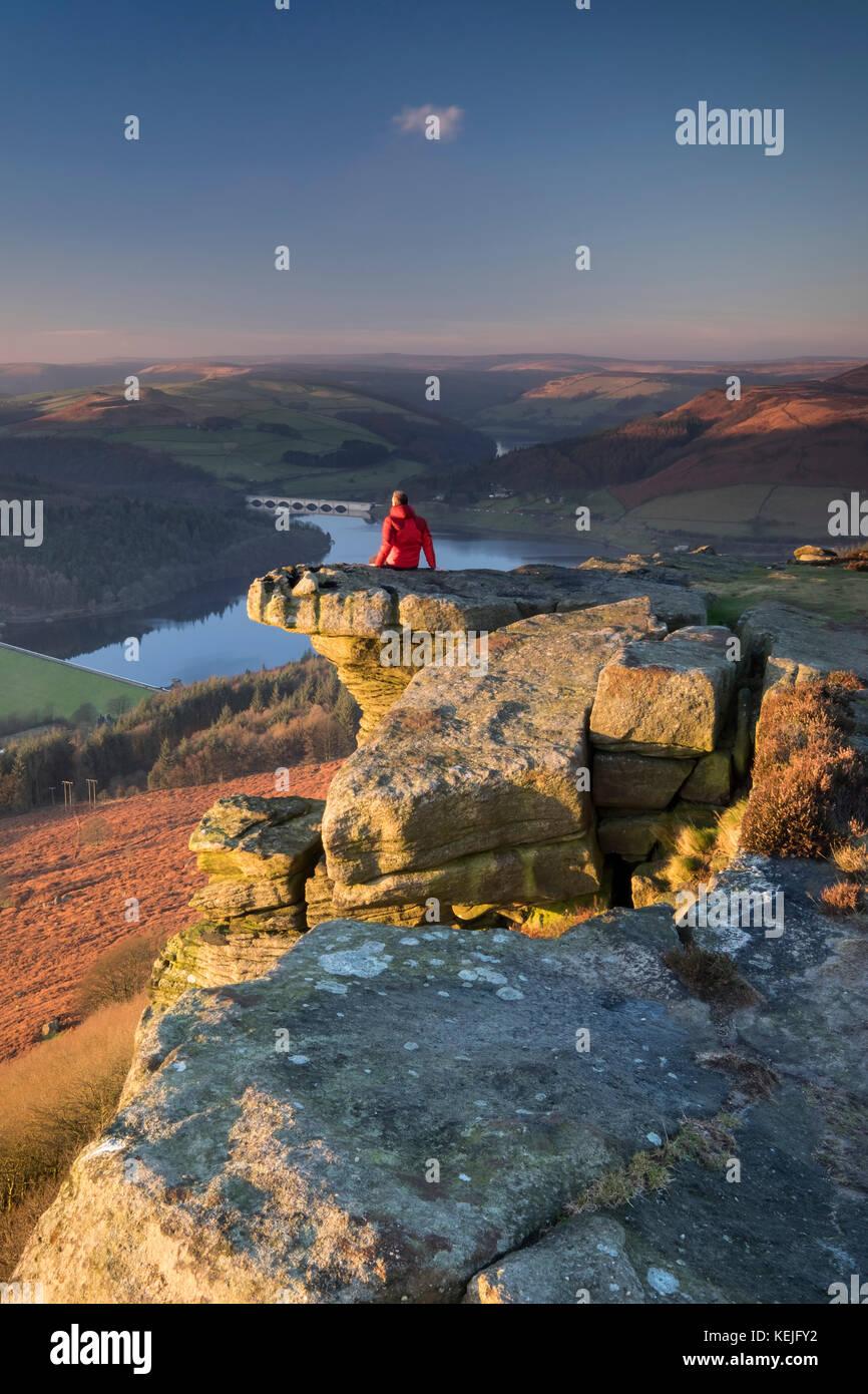 Walker sitting on Bamford Edge above Ladybower Reservoir, Peak District National Park, Derbyshire, England, UK MODEL - Stock Image