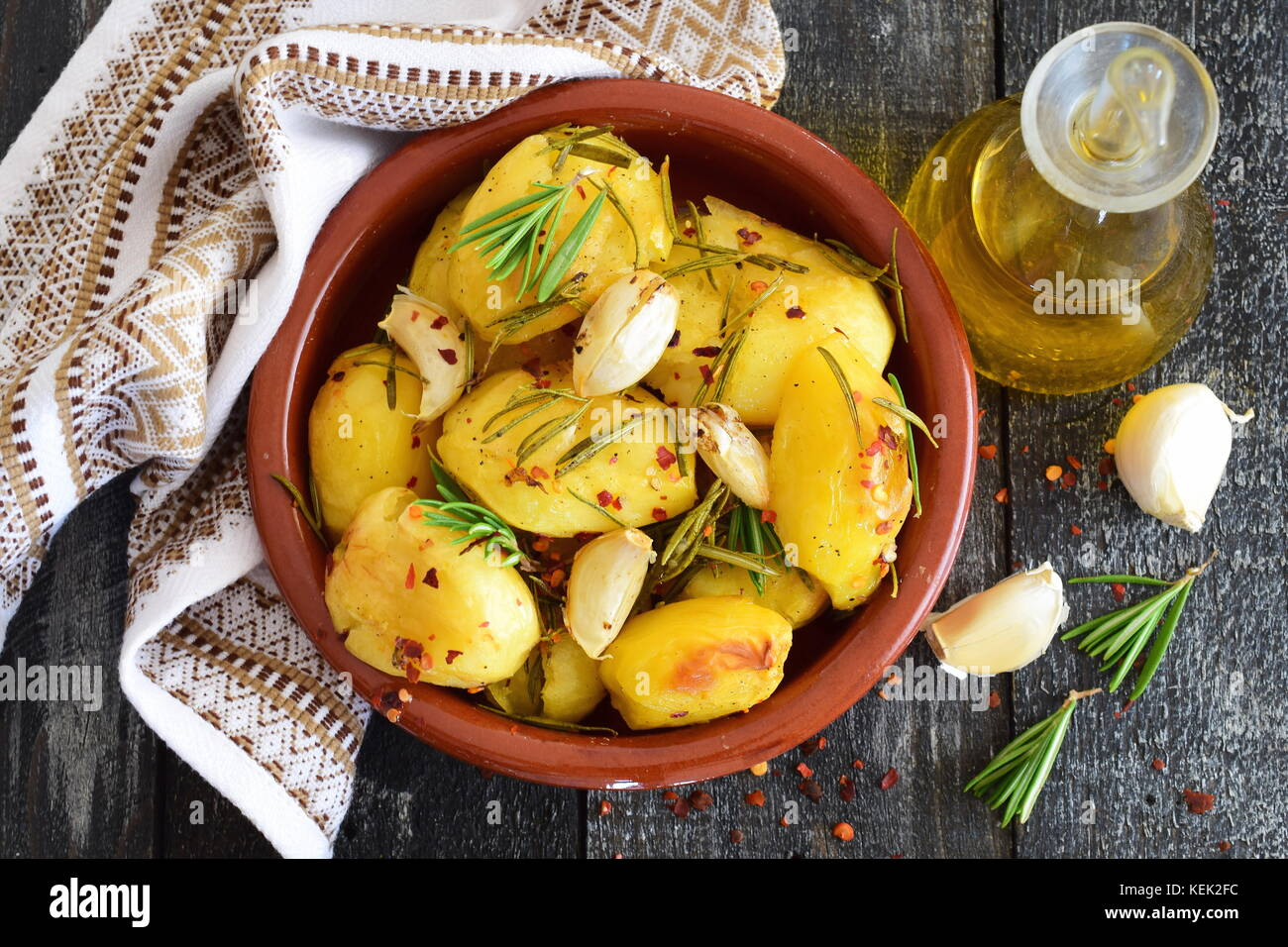 Oven cooked potato with rosemary, garlic, olive oil and mix of spices in a traditional ceramic bowl. Mediterranean - Stock Image