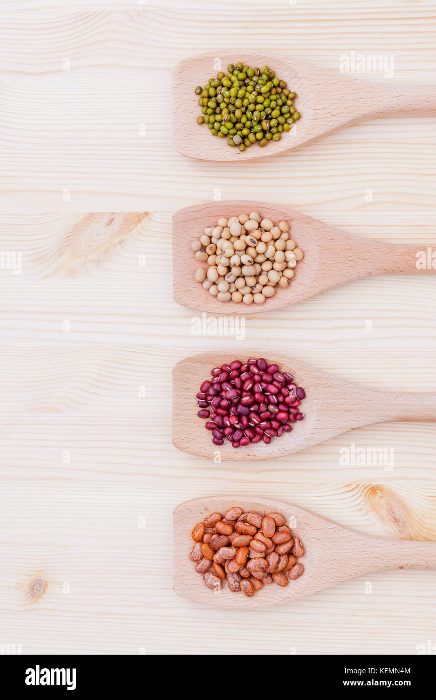 Assortment of beans and lentils in wooden spoon on wooden background.  soybean, mung bean , red bean and brown pinto - Stock Image